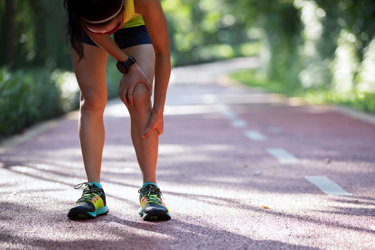 Jeune femme souffrant du genou pendant un footing