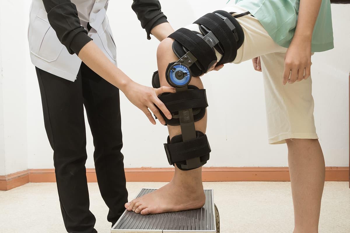 Patient portant une attelle de genou dans le cadre d'un traitement d'une entorse de genou